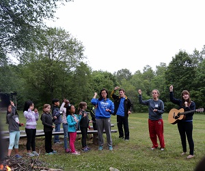 Counsellors lead campers in singing worship songs outside.