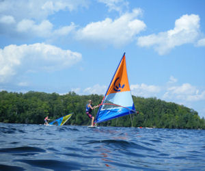 A camper balances on a windsurfer during free swim.